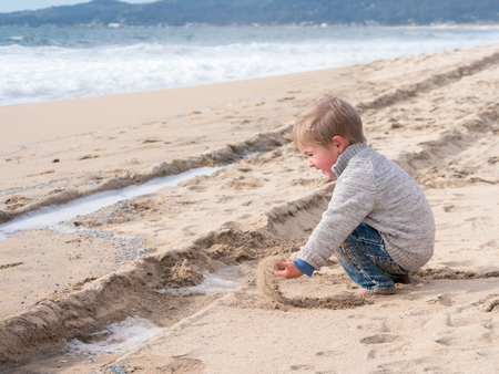 Happy boy playing in sand on the beach on vacation
