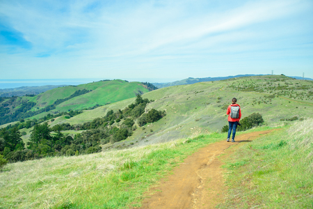Hiker woman in red jacket with backpack on trail in beautiful landscape with green hills and cloudy sky, travel and backpacking
