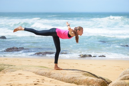 Smiling active young woman doing sports excercises on the beach