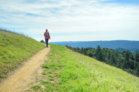 Hiker in red jacket with backpack on trail in beautiful landscape Stock Photo