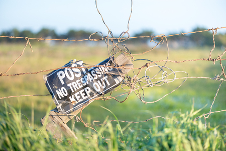 Close up of barbed wire fence with no trespassing sign on private ranch 版權商用圖片