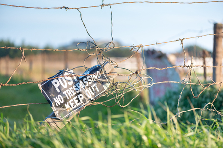Close up of barbed wire fence with no trespassing sign on private ranch Stock Photo