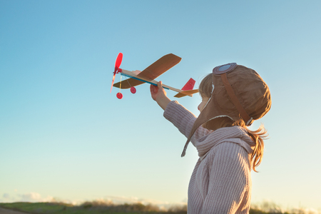 Girl in aviator hat playing pilot with toy plane outside