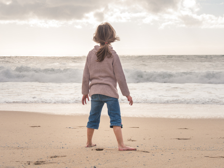 Girl standing on the beach looking at the ocean