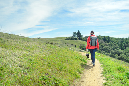 Hiker in red jacket with backpack on trail in beautiful landscape 版權商用圖片