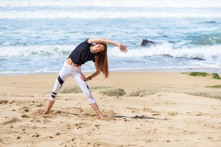 Smiling active young woman doing sports exercises on the beach Standard-Bild