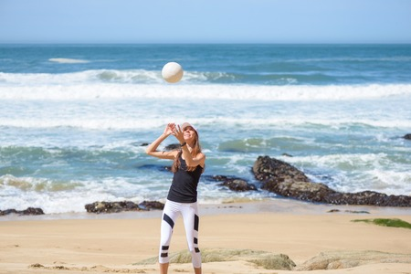 Active young woman on the beach with volleyball ball