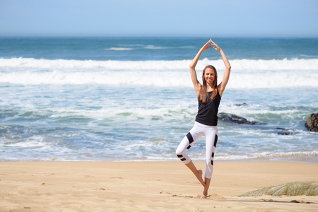 Smiling active young woman doing sports exercises on the beach 版權商用圖片