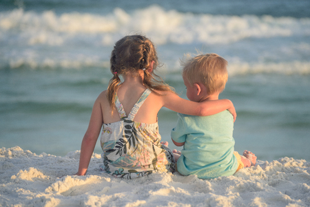 Boy and girl playing on the beach at sunset Standard-Bild