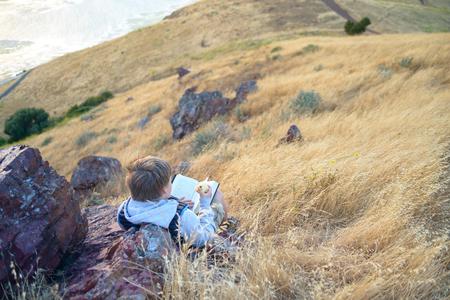 Boy reading book outside