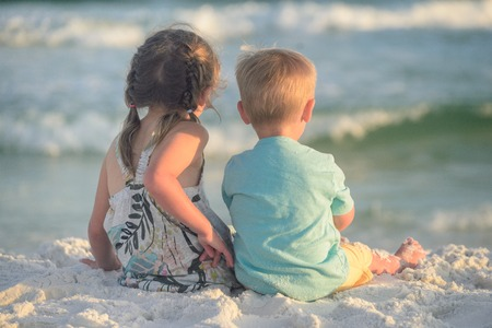 Boy and girl playing on the beach at sunset Stock Photo