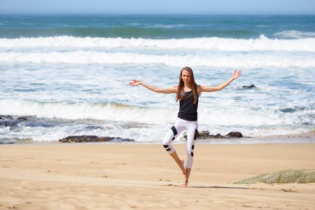 Smiling active young woman doing sports exercises on the beach Stock Photo