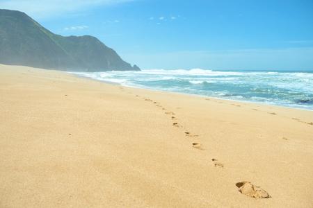 Footprints on deserted empty beach Stock Photo