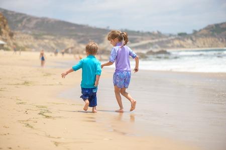 Happy kids running on the beach near the ocean Standard-Bild