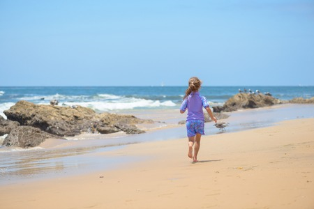 Happy girl running on the beach to the ocean