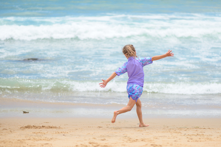 Happy girl running on the beach pretending to fly