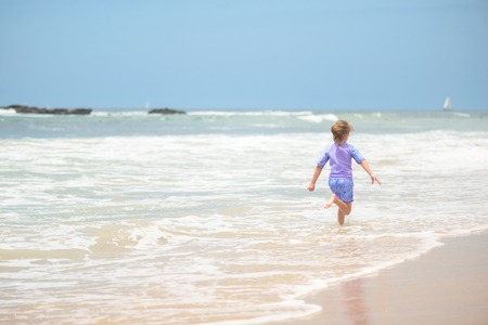 Happy girl running on the beach in the waves