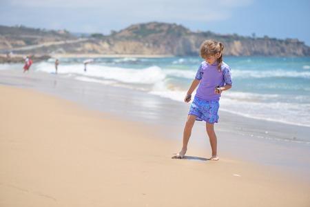 Happy girl playing on the beach near the ocean