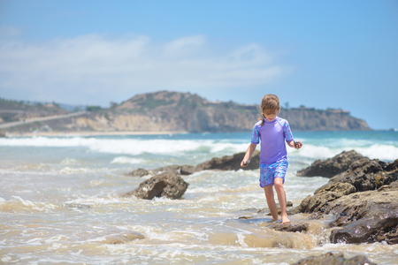 Happy girl playing on the beach in the rocks