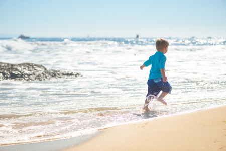 Happy boy running on the beach in the waves 版權商用圖片