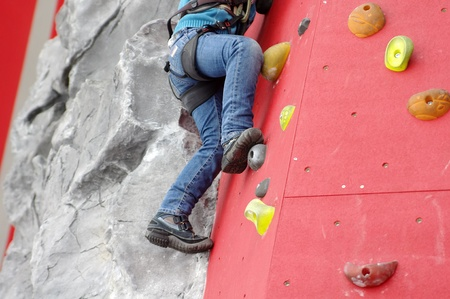Child climbing on a wall in a climbing center Stock Photo - 8494718