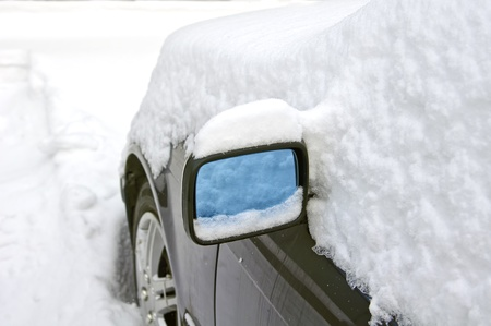 Heavy snow around car mirror