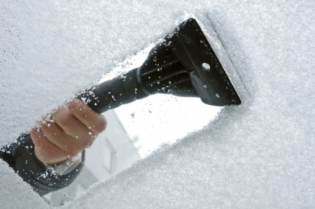 scraping snow and ice from the car windscreen  photo