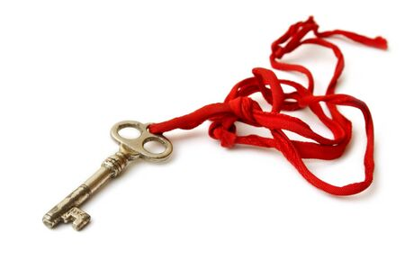 Old Key on a white background with red string Stock Photo - 8577125