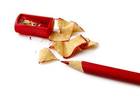 Red pencil and wood waste on white background photo