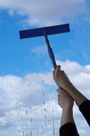 squeegee: Hands with squeegee cleaning the misted window  Stock Photo