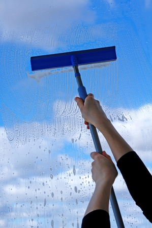 squeegee: Hand with squeegee cleaning the misted window  Stock Photo