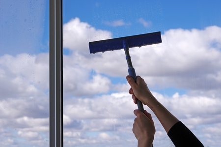 Hands with squeegee cleaning the misted window  Stock Photo
