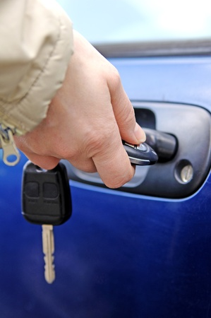 car lock: Hand opening the car door with a remote control  Stock Photo