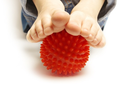 Child foots with spiny plastic orange massage ball on white background  Stock Photo