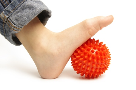 anklebone: Child foot with spiny plastic orange massage ball on white background