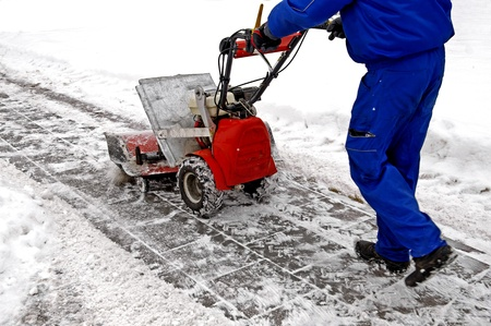 clean street: Man working with a snow blowing machine v