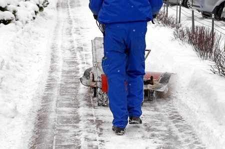 Man working with a snow blowing machine