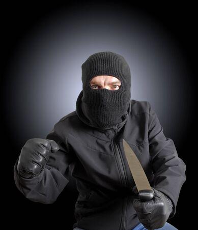 Masked criminal holding a knife  photo