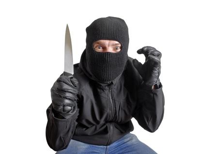 Masked criminal holding a knife, isolated on white   photo