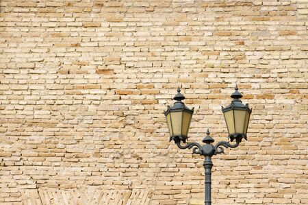 Old style street lamp in front of the wall of yellow bricks  photo