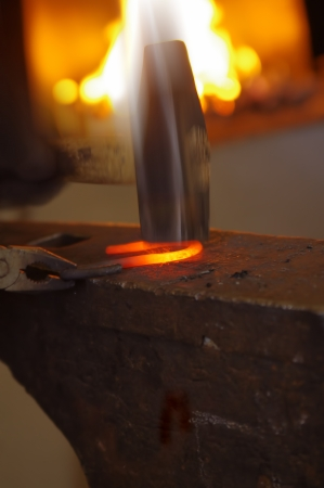 Blacksmith is working with his hammer  photo