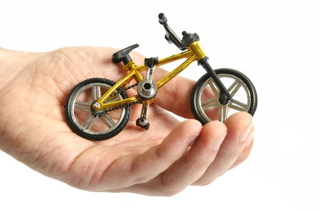 A small toy bicycle in hand  photo