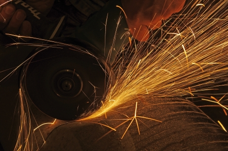 tool and die: Metal sawing. Hot sparks at grinding steel material.  Stock Photo
