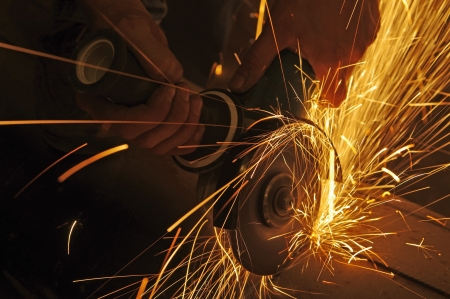 Metal sawing. Hot sparks at grinding steel material.  Stock Photo