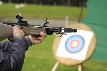finger on trigger: Man aiming crossbow at targets