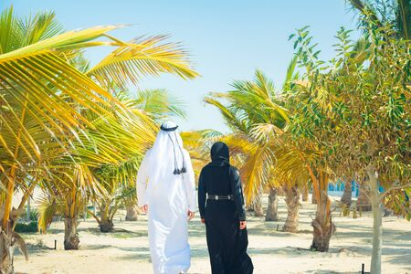 agal: Arabian Couple Walking Among Palm Trees Stock Photo