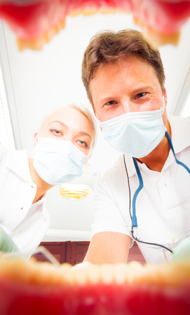 looking into: Dentist And His Assistant Looking Into Your Mouth