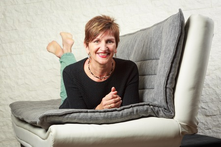 woman on couch: Senior Woman Sitting On Couch Stock Photo