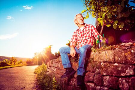 colored bottle: Winemaker Sitting By His Vineyard Stock Photo