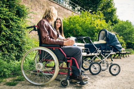 daddy long legs: Young Parents In Wheelchair With Baby Stroller In The Park